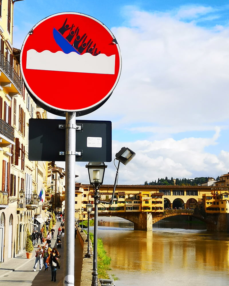 Clet's sign with the Ponte Vecchio in the background